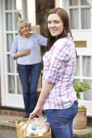 caregiver delivering food to senior woman